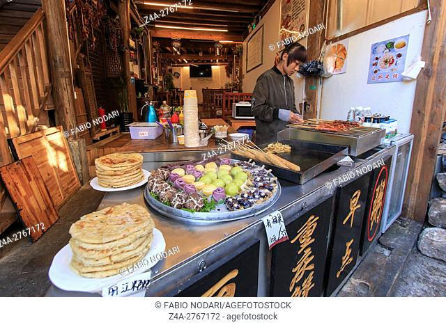 Woman preparing some traditional Chinese snaks in Lijiang Old Town, China