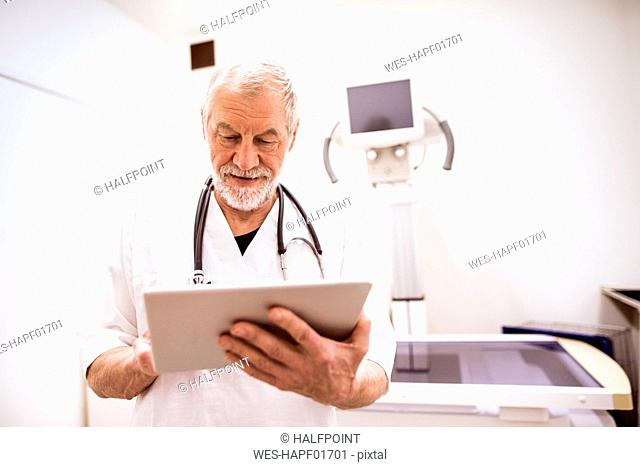Senior vet using tablet in clinic