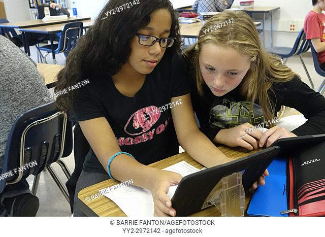 7th Grade Girls Looking at iPad in Classroom, Wellsville, New York, USA
