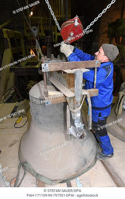 Bell technician Udo Griwahn transports a 1.7 ton heavy bronze bell into the tower of the St. Petri church in Wolgast, Germany, 09 November 2017
