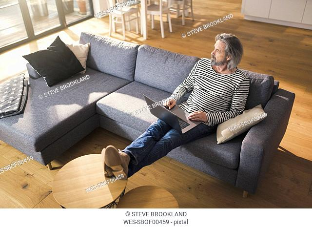 Senior man sitting on couch, using laptop