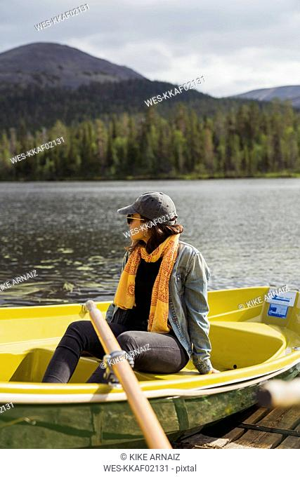 Finland, Lapland, woman sitting in a boat on a lake