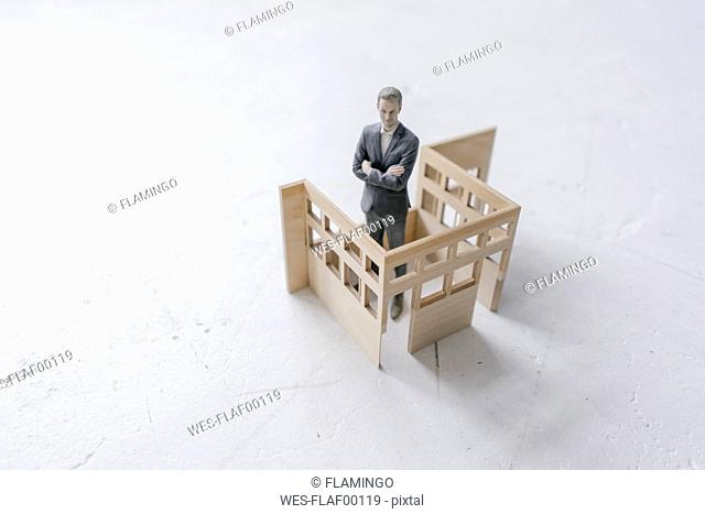 Miniature businessman figurine standing in architectural model