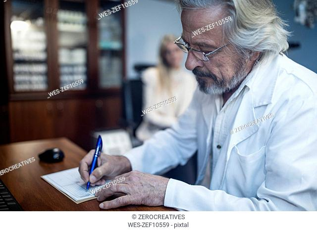 Ophtalmologist writing medical record of patient
