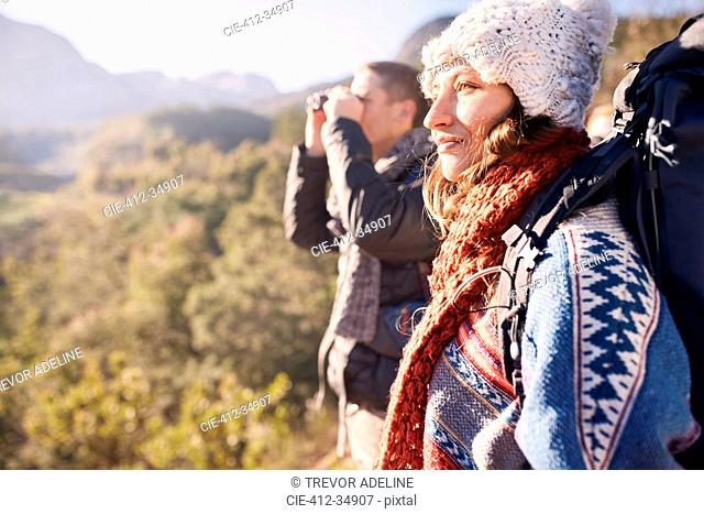 Young couple hiking, looking at sunny view with binoculars