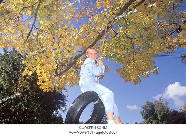 A girl on a tire swing in autumn, New England