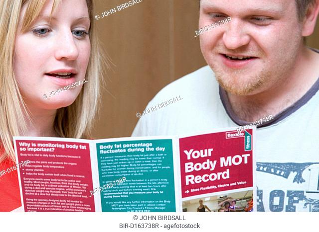 Fitness instructor going through a body MOT leaflet with a member at his sports leisure centre