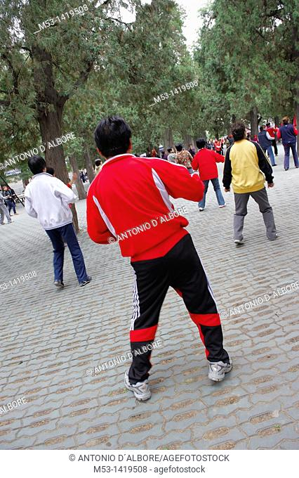People performing morning dance-aerobic in the park of Temple of Heaven  The men wearing the red and black sport suite lead the group showing body movements and...