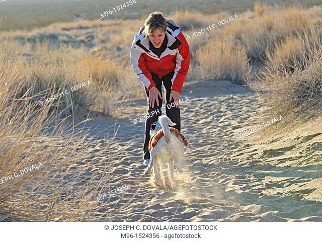 Happy woman and mixed breed dog, Providence Mountains, Mojave Desert, California, USA