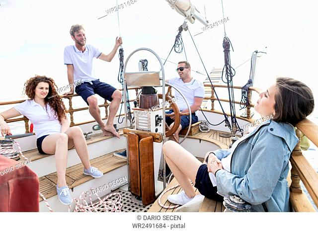 Group of friends relaxing on sailboat