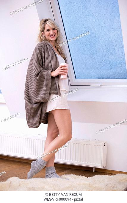 Young woman standing at window with coffee, smiling, portrait
