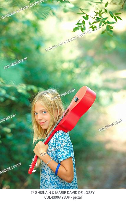 Portrait of girl with red ukulele in woodland, Buonconvento, Tuscany, Italy