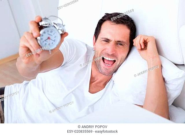 Exhausted Man Being Awakened By An Alarm Clock