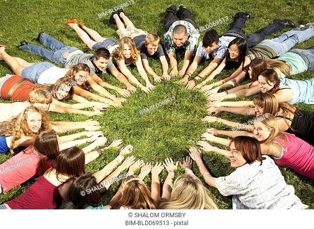 Teenagers laying in a circle with arms pointing towards middle outdoors