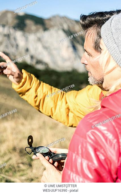 Austria, Tyrol, couple with compass hiking in the mountains