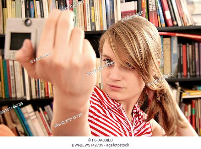 young woman in front of books takes a photo of herself