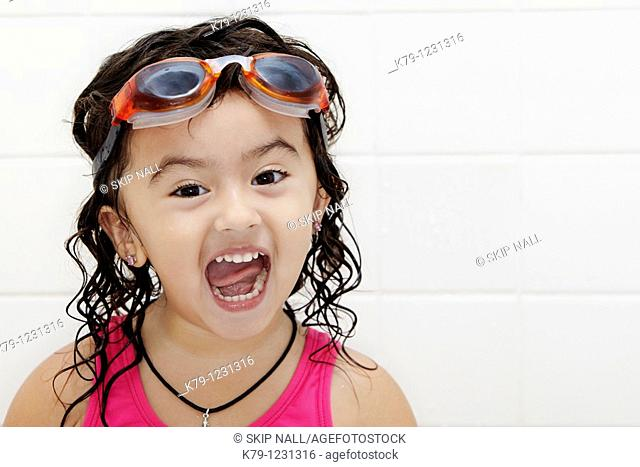 Little girl in swim suit and swim goggles with excited look on her face