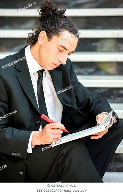 Man in suit sitting at stairs with newspaper and searching job