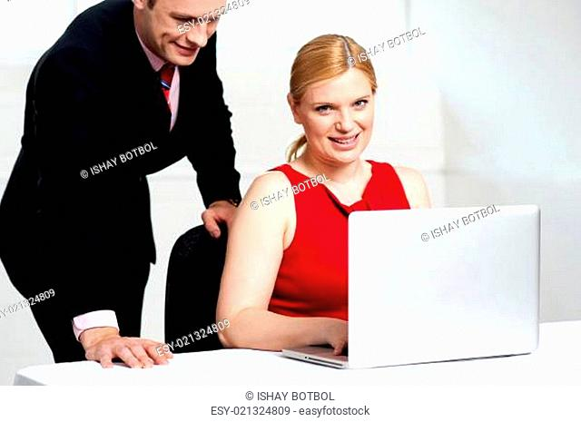 Trendy female boss working with man assisting