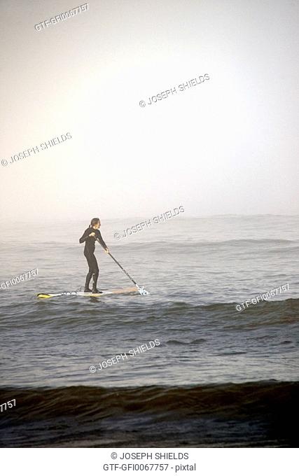 Woman paddleboarding in the fog