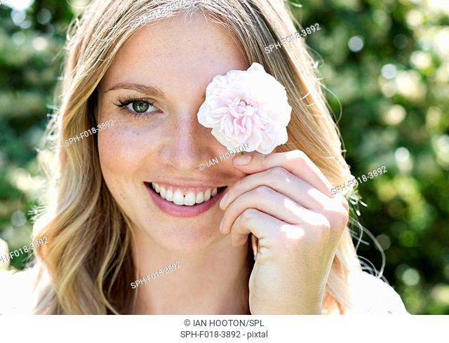 MODEL RELEASED. Young woman holding flower in front of eye