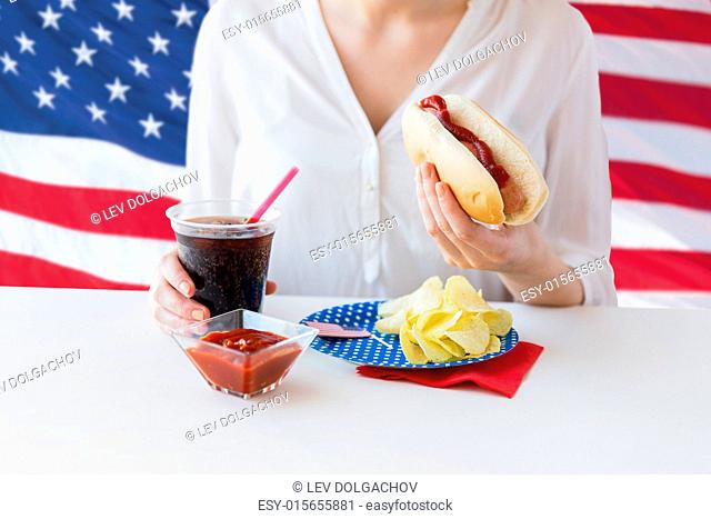 american independence day, celebration, patriotism and holidays concept - close up of woman hands holding hot dog and coca cola in plastic cup with potato chips...