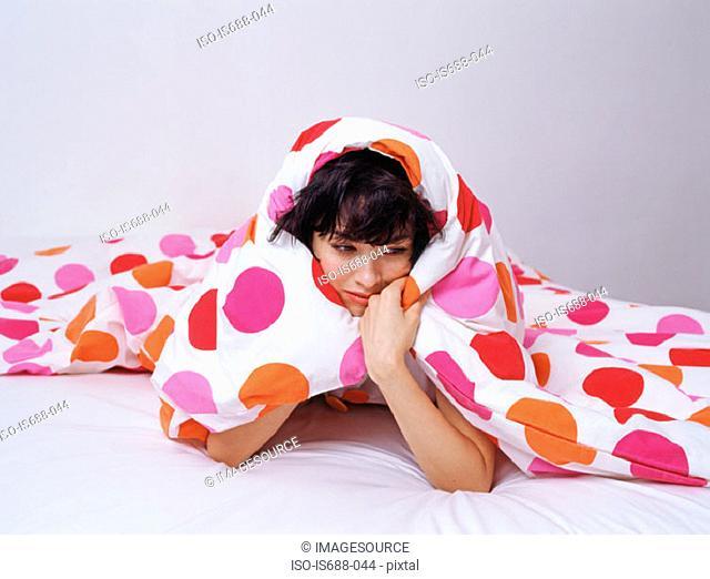 Woman under her duvet