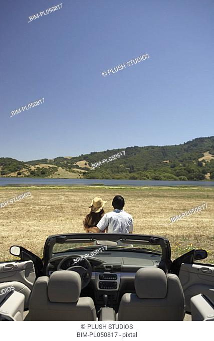Couple sitting outdoors with convertible in foreground