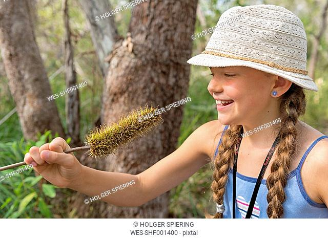 Australia, New South Wales, Pottsville, girl with hat with an Australian Banksia plant flower