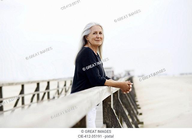 Portrait confident senior woman leaning on beach boardwalk railing