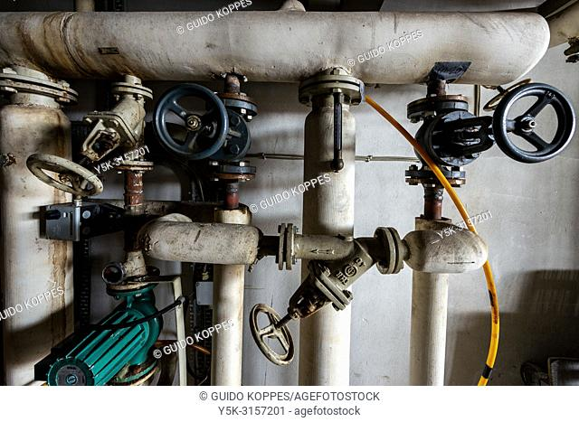 Rotterdam, Netherlands. Central heating installation with taps and pipes inside an old, 1950's build industrial and harbour cantina for employees on the dock's...