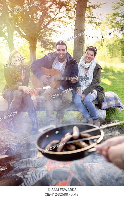 Friends with guitar cooking hot dogs over campfire