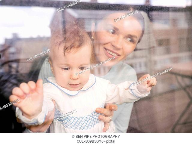Mother and baby looking through glass window