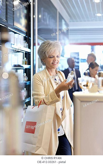 Woman shopping for perfume in airport duty free shop