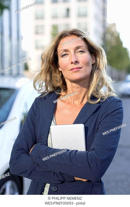 Portrait of confident businesswoman holding tablet in the city