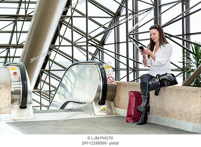 Business woman texting on her smart phone after taking a shopping break during her work day; Edmonton, Alberta, Canada