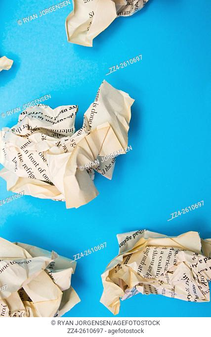 Object photograph of scrunched up text book pages scattered abstractly in crumpled sheet of paper thin fiction. Here lies our history