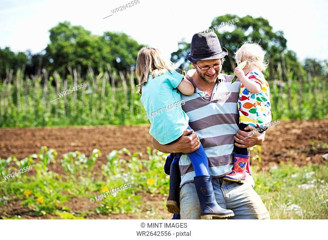A man carrying two children in a field