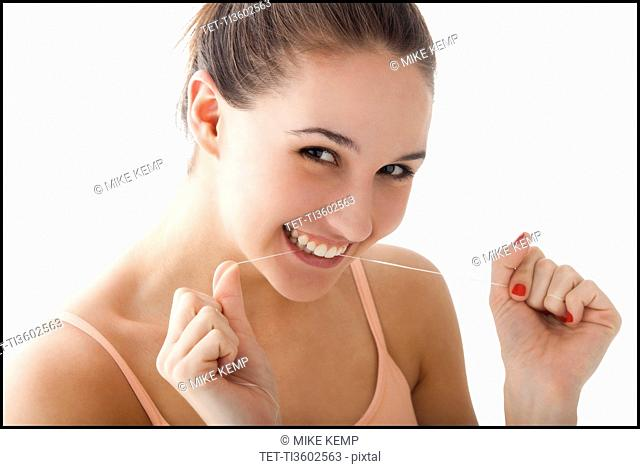 Studio portrait of young woman flossing teeth