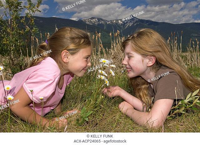 Two young girls enjoy the wildflowers on a summer's day, Valemount, Thompson Okanagan region, British Columbia, Canada