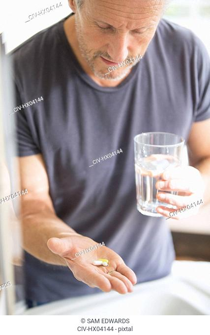 Mature man taking vitamins with glass of water
