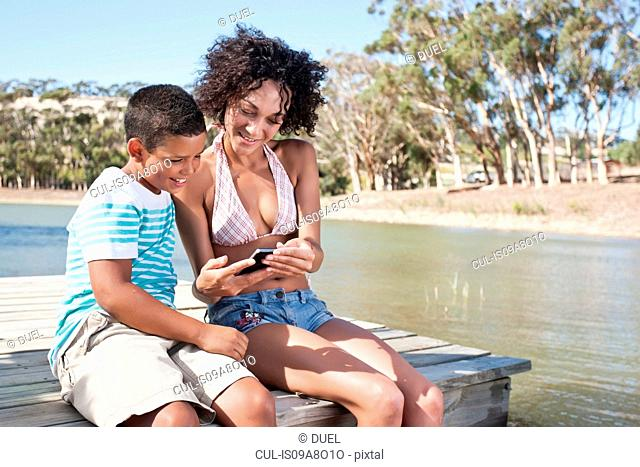 Woman and boy sitting on pier looking at photos on camera