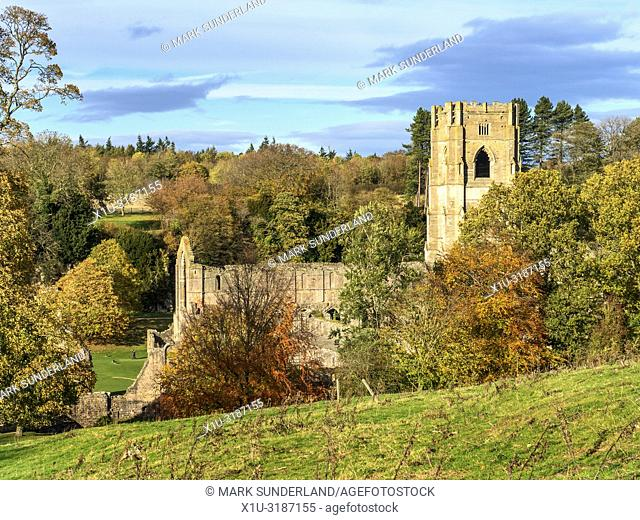 Fountains Abbey amongst autumn trees from Abbey Wall path near Ripon North Yorkshire England