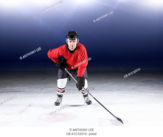 Portrait determined hockey player in red uniform on ice