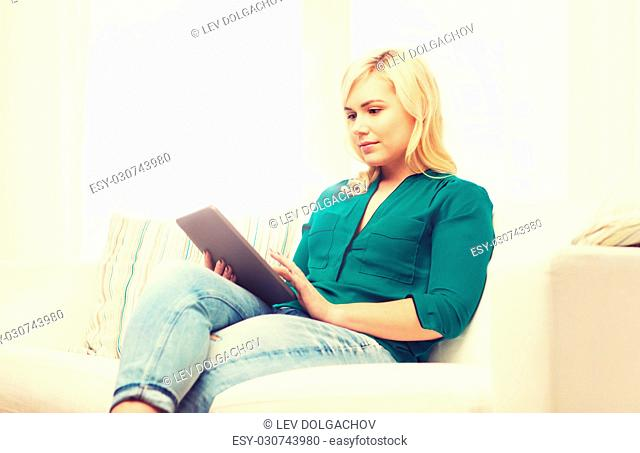 technology, internet and people concept concept - smiling woman sitting on couch with tablet pc computer at home