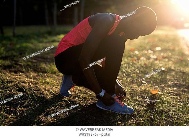 Female athlete tying her shoe lace