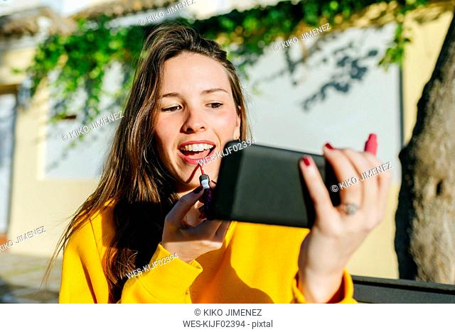 Young woman applying lipstick looking at herself on the cell phone