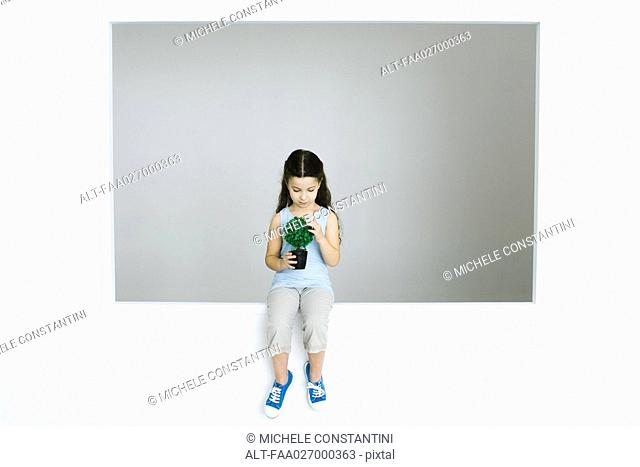 Little girl sitting, holding potted plant, looking down