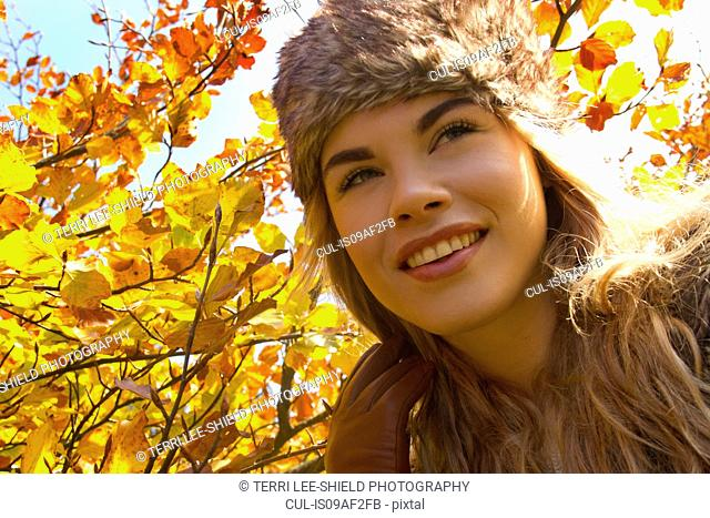 Young woman in fur hat in autumnal park