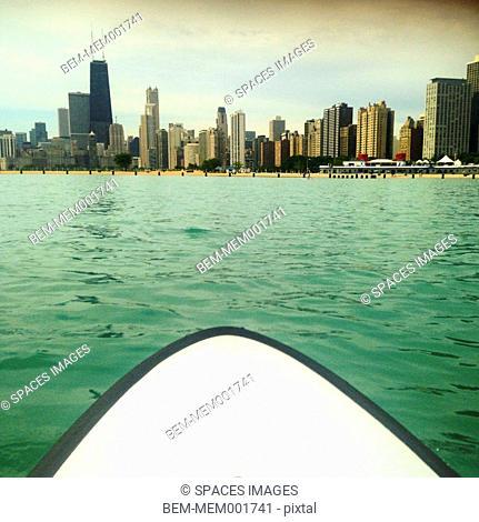 Paddleboard pointing towards Chicago city skyline, Illinois, United States
